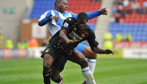 Micah Tussles with Wigan Titus Bramble for the ball
