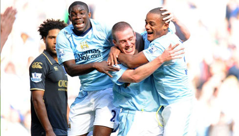 Richard Dunne celebrates scoring City's second goal with teammates Vincent Kompany and Micah.