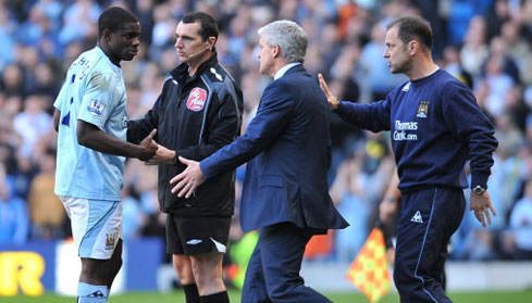 Micah Richards receives directions from manager Mark Hughes