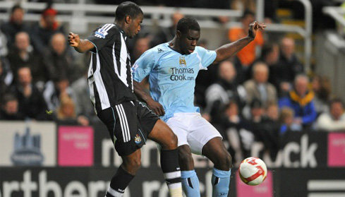 Micah Richards and Newcastle United's Sebastien Bassong battle for the ball